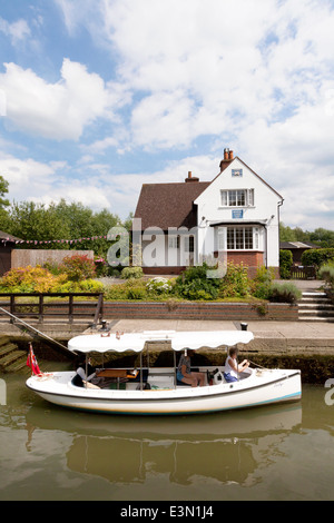A boat in Benson Lock, with the lock house, Benson Lock, River Thames, Oxfordshire England UK - Stock Photo