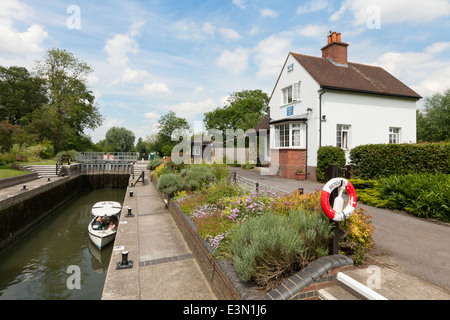 A boat in Benson Lock, with the lock house, River Thames, Oxfordshire, England UK - Stock Photo