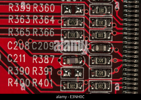 Macro-photo of a small section of a PC motherboard showing surface mounted (SMT) resistors and capacitors. Wiring - Stock Photo