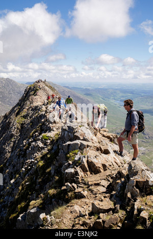 View back along Crib Goch ridge scramble with hikers scrambling at start of Snowdon Horseshoe in mountains of Snowdonia - Stock Photo