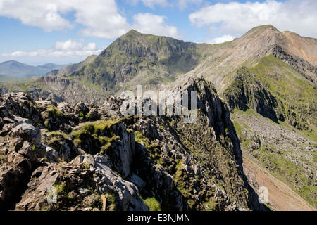 View along Crib Goch ridge scramble to Pinnacles with Crib y Ddysgl and distant Snowdon summit in the horseshoe. - Stock Photo