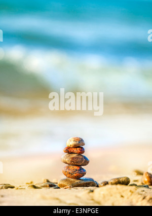 Stones pyramid on sand symbolizing peace and harmony, blue ocean in the background . - Stock Photo