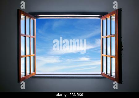 Wide open rustic window showing a blue sky outside - Stock Photo