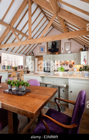 Open plan kitchen diner with pitched roof and beamed ceilings. The dining chairs are upholstered in Maya by Manuel - Stock Photo