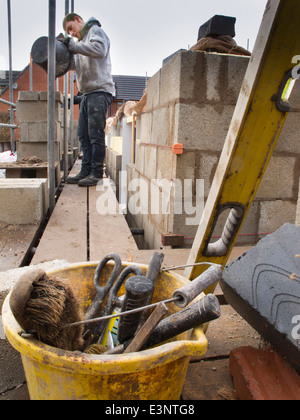 self building house, bricklayers on scaffolding laying upper floor exterior concrete blocks mixing mortar - Stock Photo