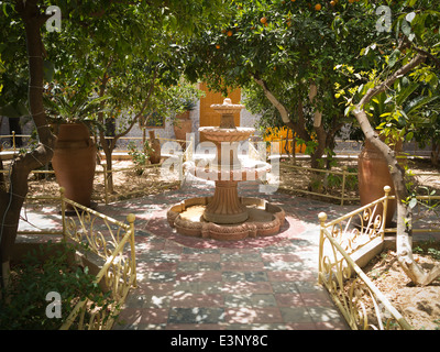 A four tiered stone fountain without water in a shady garden surrounded by orange trees Riad el Aissi Taroudant - Stock Photo