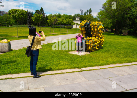 Mother photographing her child in front of sculpture made up of 400 gas masks on May 10 2014, NKD park, Sofia, Bulgaria - Stock Photo