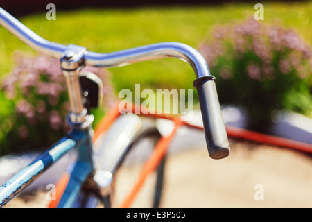 Vintage bicycle handlebar detail close up with parking bokeh background in flower bed in sunny day - Stock Photo