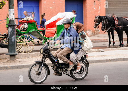 A man and a women ride along the street on a small 50cc motor scooter, Marrakech, Morocco - Stock Photo