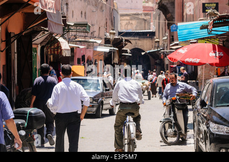 Lots of people on various modes of transport going along a narrow street in the Medina, Marrakech, Morocco - Stock Photo