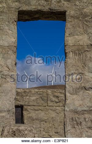 Two Wind Turbines Seen Between Pillars At Stonehenge Replica In Washington State, USA - Stock Photo