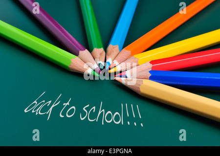 sentence back to school and some pencil crayons of different colors on a green chalkboard - Stock Photo