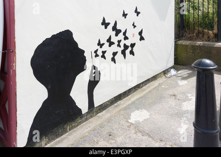 A Graffito of a boy blowing bubbles that are butterflies flying away - Stock Photo