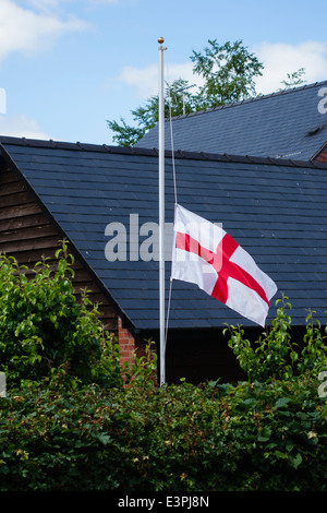 An English flag (the St George's Cross) flies at half mast after England's defeat in the 2014 Football World Cup - Stock Photo