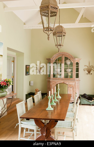 Old French farmhouse table in dining room with Swedish style chairs and antique French cupboard - Stock Photo