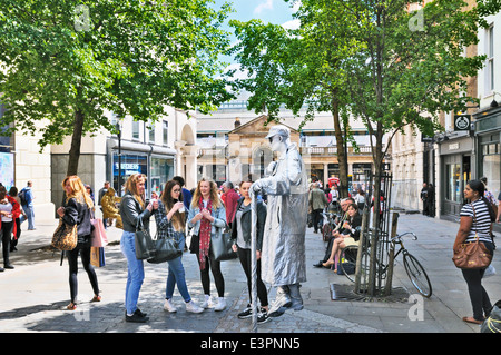 Human statue sparks the curiosity of a group of teenage girls in Covent Garden, London, England, UK - Stock Photo