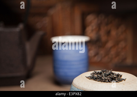 Green tea leafs with pot and cup in background depicting health with warm rustic pottery and iron tea pot. - Stock Photo