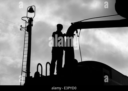 The fireman of a steam train filling up with water. - Stock Photo