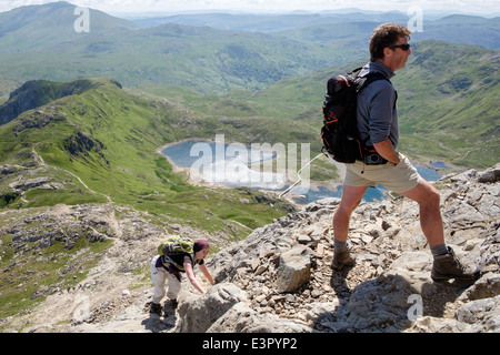 Hikers scrambling up Crib Goch at start of Snowdon Horseshoe in mountains of Snowdonia National Park on a mid summer - Stock Photo