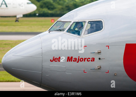 Pilot looking out of the cockpit windows of a Jet 2.com Boeing 737 aircraft as it passes at Manchester Airport - Stock Photo