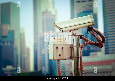 Vintage retro hipster style travel image of CCTV surveillance camera in Singapore with skyscrapers in background - Stock Photo