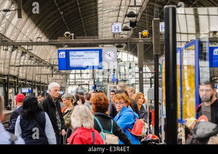 Passengers wait on a platform in Amsterdam Centraal Station for a train - Stock Photo