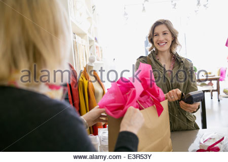 Woman using credit card reader in shop - Stock Photo