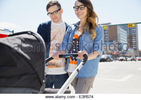 Hipster couple pushing stroller on sunny urban street - Stock Photo