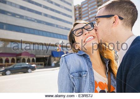 Enthusiastic couple kissing on sunny urban street - Stock Photo