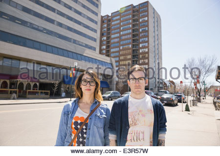 Portrait of hipster couple on sunny urban street - Stock Photo