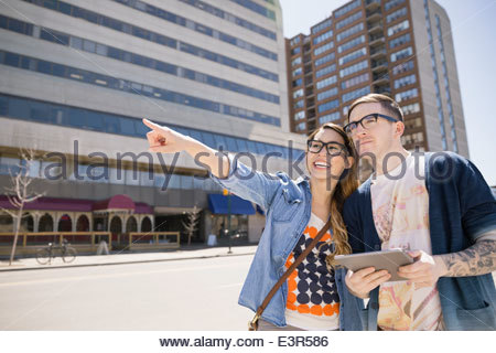 Hipster couple with digital tablet on urban street - Stock Photo
