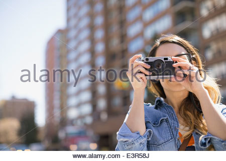 Woman using camera in city - Stock Photo