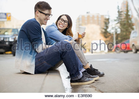 Hipster couple drinking coffee on urban curb - Stock Photo
