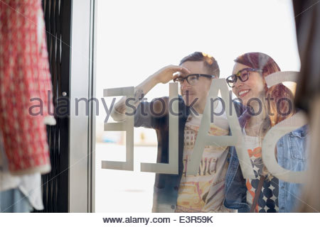 Hipster couple window shopping at storefront - Stock Photo