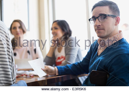 Portrait of man with menu in bistro - Stock Photo