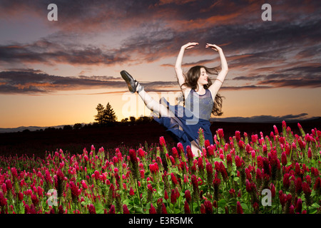 Ballerina dancing in a clover field at sunset - Stock Photo