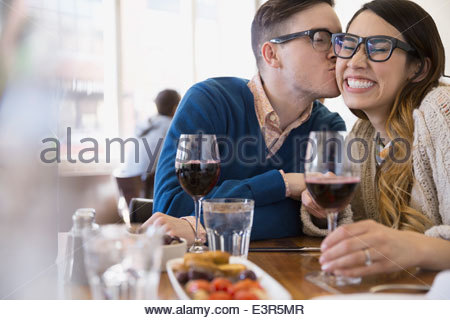 Couple with wine kissing in bistro - Stock Photo