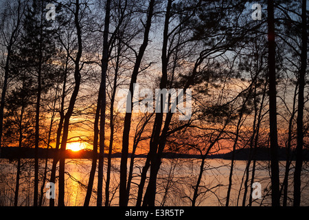 Sunset on Saimaa lake in Finland with silhouettes of trees - Stock Photo