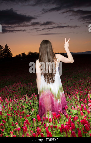 Young women in a clover field at sunset - Stock Photo