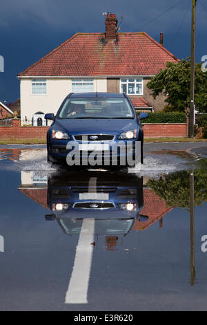 Caister-On-Sea, Norfolk, UK. 27th June 2014. Localised flooding on roads at Caister-On-Sea in Norfolk after cloudburst. - Stock Photo