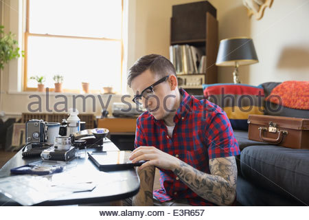 Man using digital tablet in living room - Stock Photo