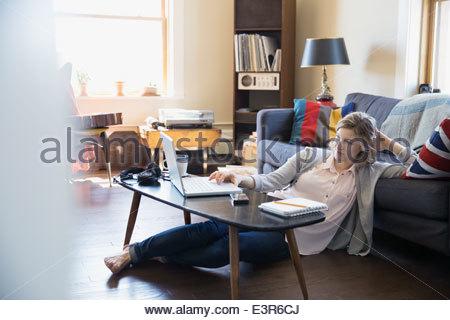 Woman using laptop on living room floor - Stock Photo