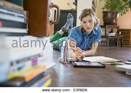 Woman with digital tablet drawing on floor - Stock Photo