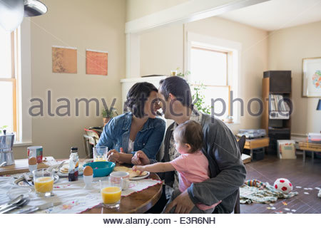 Young family enjoying breakfast at dining table - Stock Photo