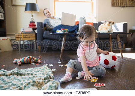 Father with laptop watching baby daughter play - Stock Photo