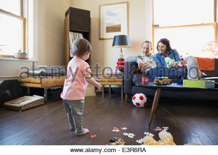 Parents watching baby daughter play with soccer ball - Stock Photo