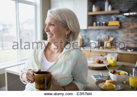 Woman drinking coffee in kitchen - Stock Photo