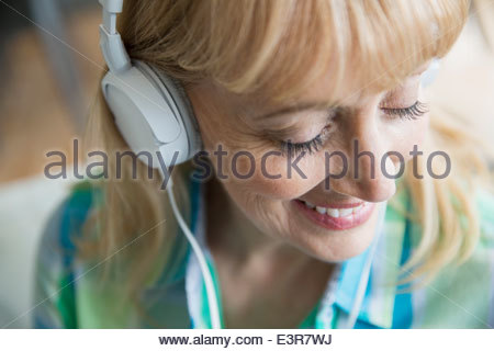 Smiling woman listening to music with headphones - Stock Photo