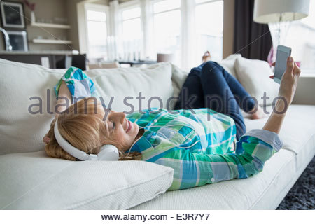 Woman laying on sofa and listening to music - Stock Photo