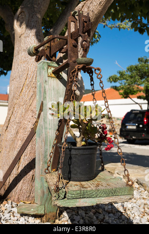 A pot plant on an old set of antique weighing scales, in the Greek island town of Skopelos. - Stock Photo